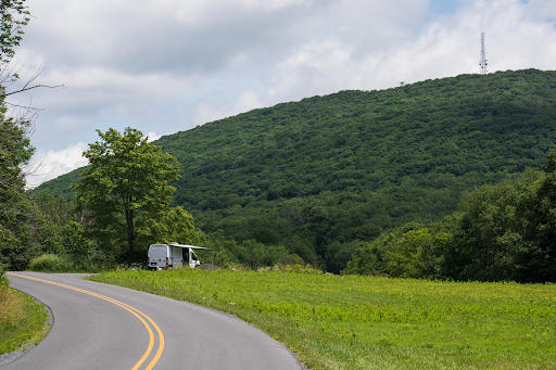 Road winding through green hills with van parked in the distance.