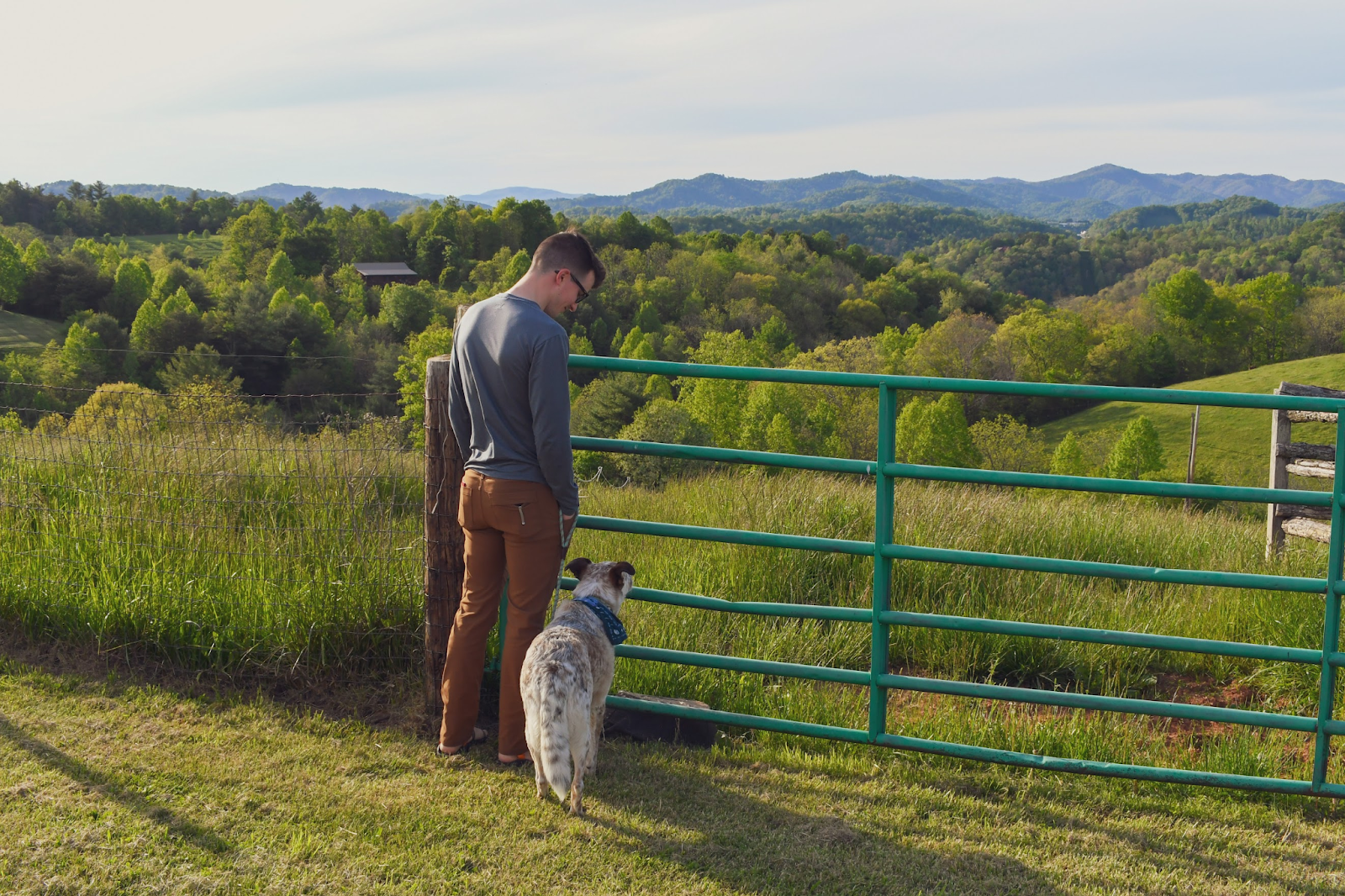 Travis and his dog standing by a green fence overlooking hills.