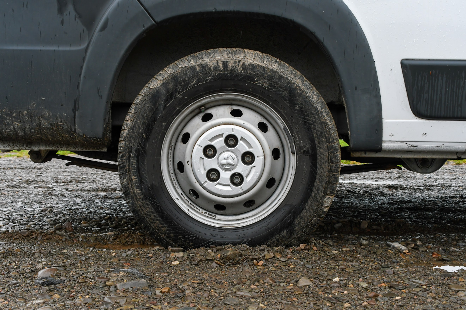Closeup of a van tire sunken in mud.