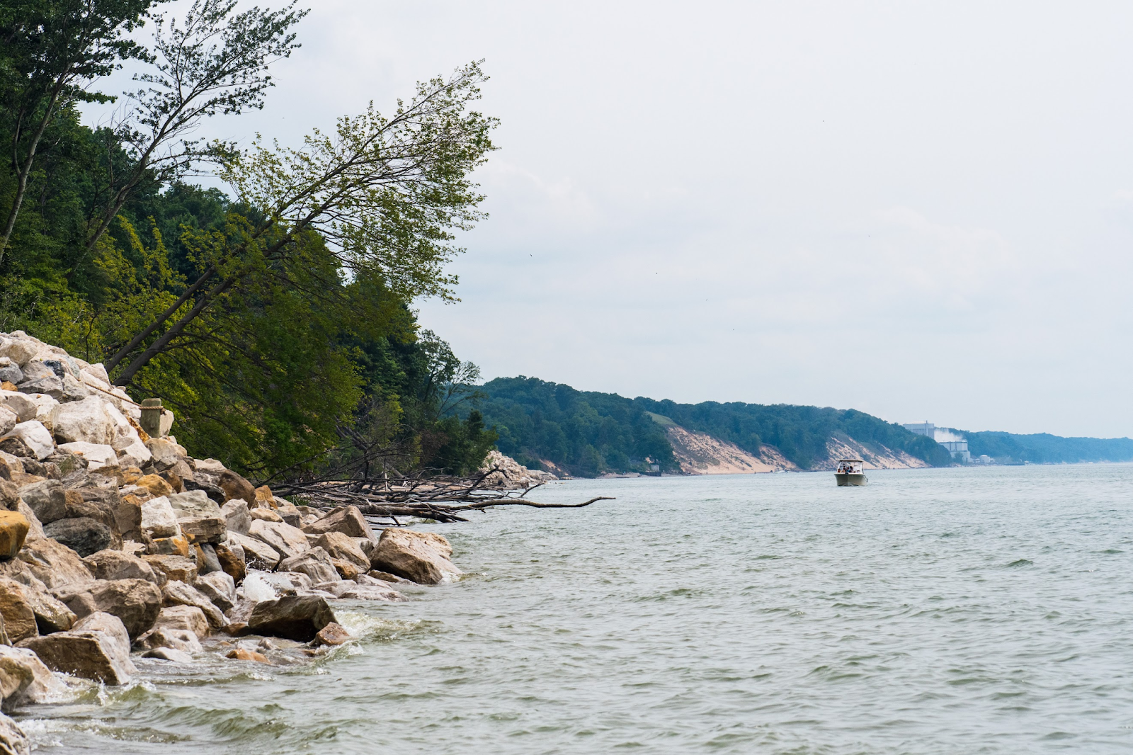 Rocky lake shoreline with forests and boat in the distance.